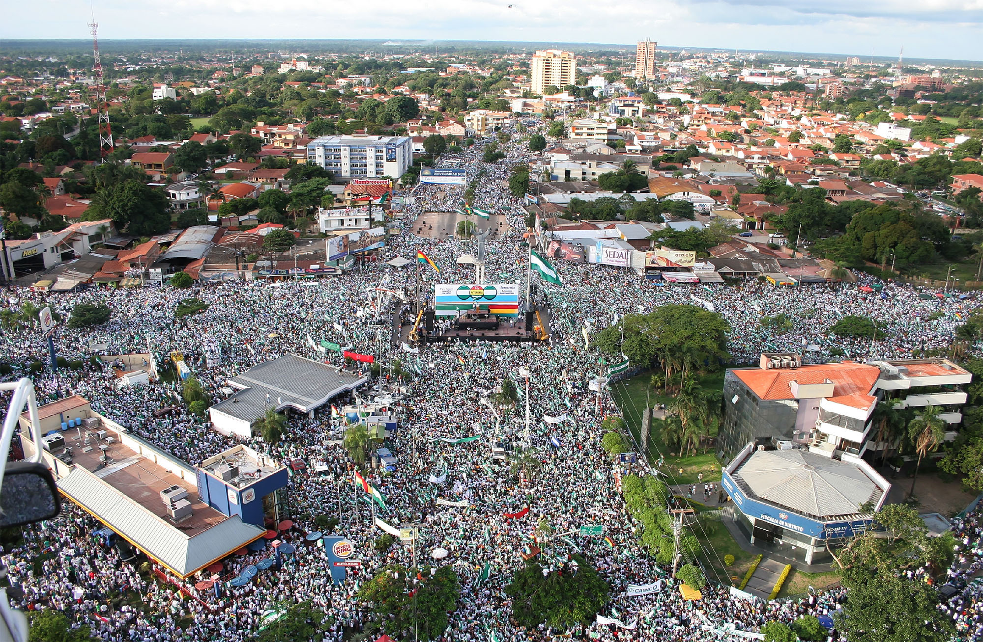 """An aerial view of a huge crowd of people in plaza in Santa Cruz, Bolivia, as part of the 2006 """"Cabildo del Millión"""" demonstration supporting autonomy for Santa Cruz within Bolivia. (Photo courtesy of the Comité Pro Santa Cruz.)"""