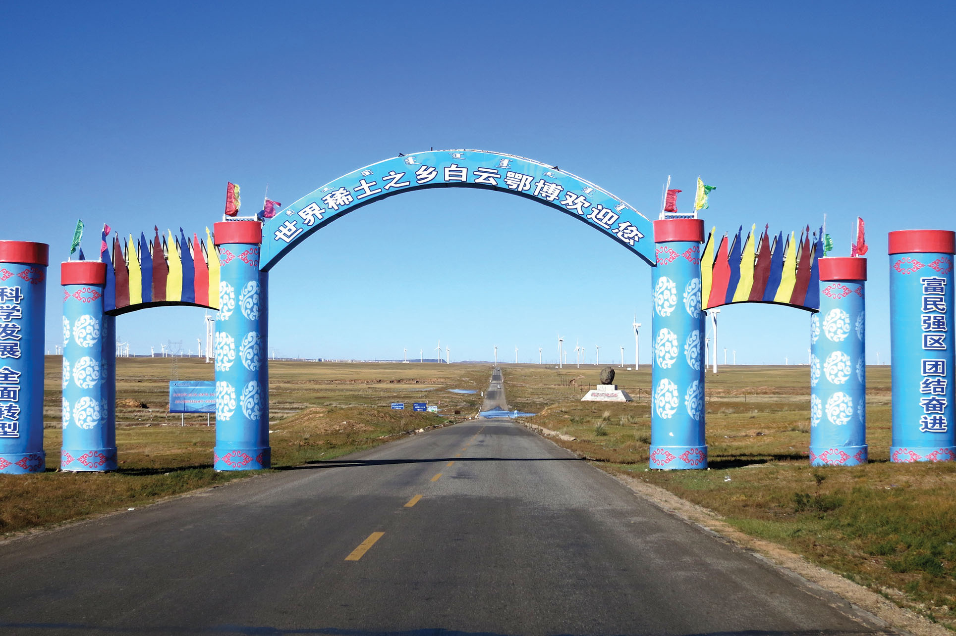 """An archway above a road reads in Chinese, """"Welcome to Bayan Obo, hometown of rare earths."""" (Photo by Julie Klinger.)"""