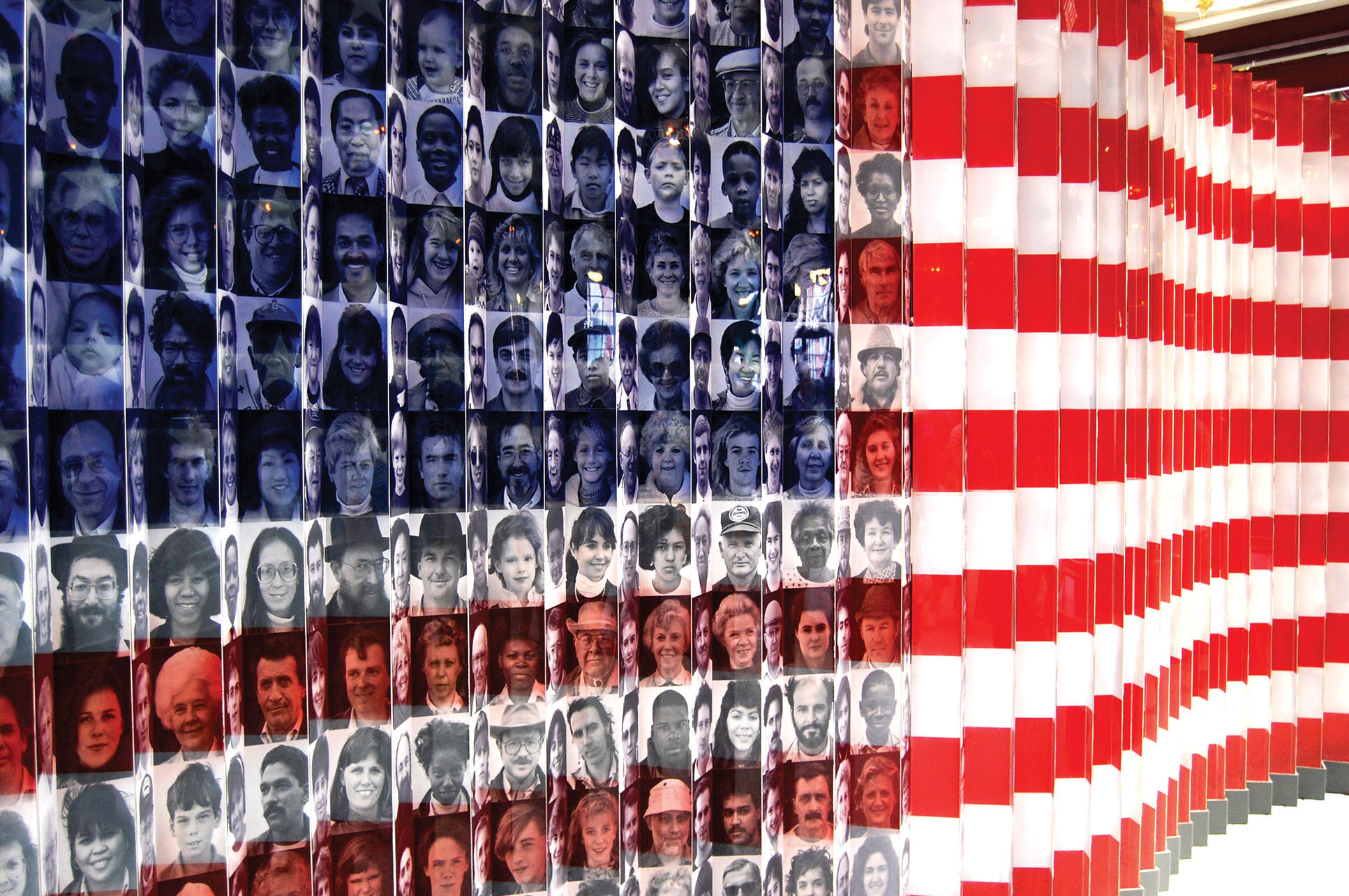 An American flag with the faces of immigrants used to form part of the design on display at Ellis Island. (Photo by Ludovic Bertron.)
