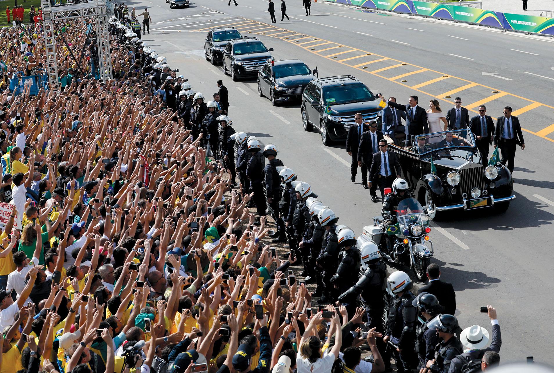 Brazilian President Jair Bolsonaro waves to supporters following his swearing-in ceremony, January 2019. (Photo by Silvia Izquierdo/AP Photo.)