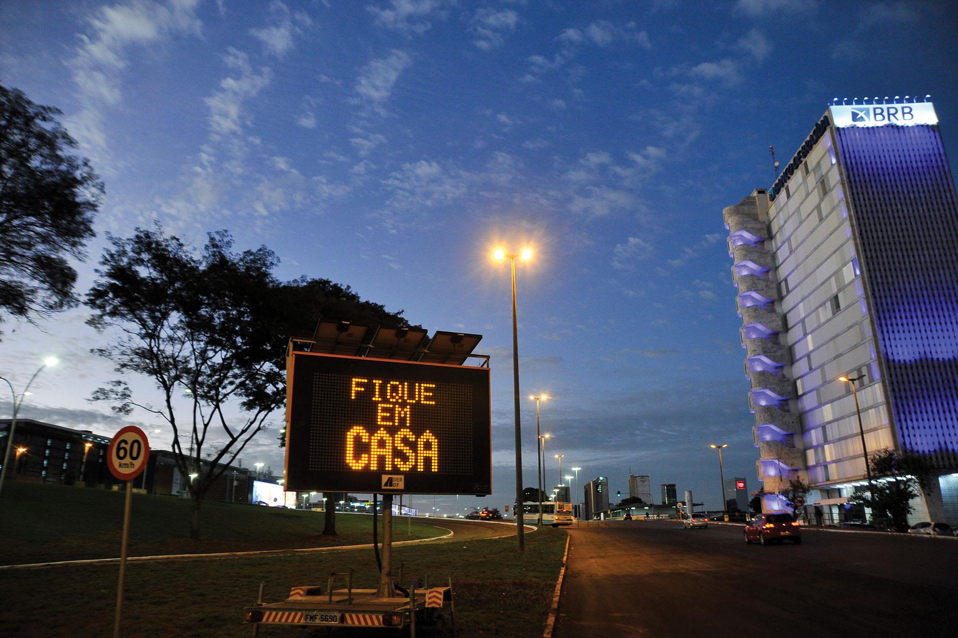 "A roadside sign in Brasilia advises residents to ""stay home"" in May 2020. (Photo by Leonardo Sá/Agência Senado.)"