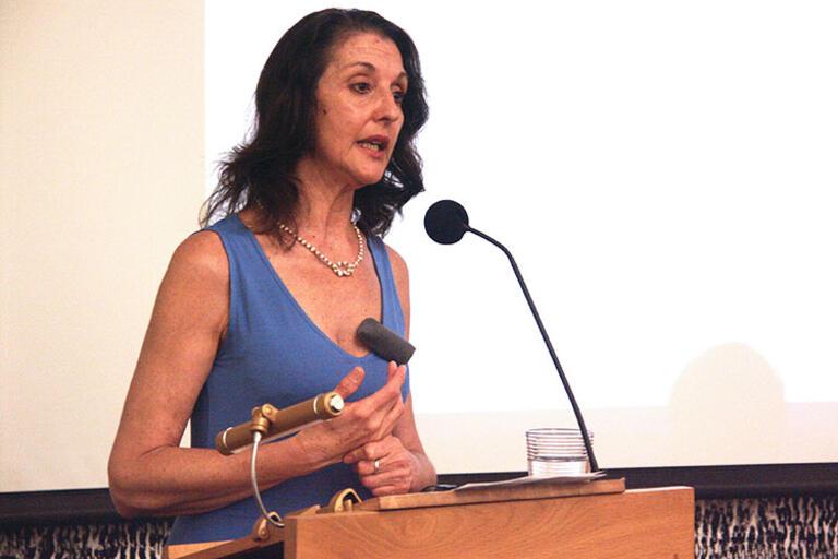 Claudia Bernardi speaking at UC Berkeley wearing a blue dress
