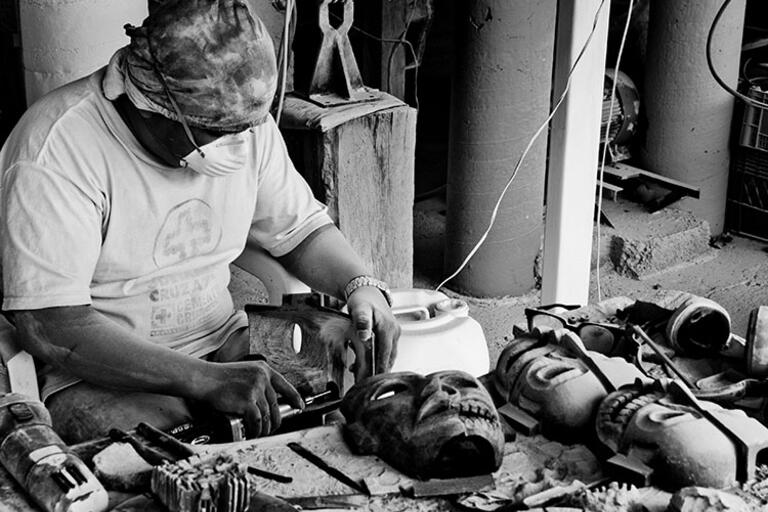 A black and white photo of a worker making masks in Teotihuacán