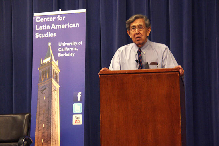 Cuauhtémoc Cárdenas speaking at UC Berkeley, standing in front of a CLAS banner