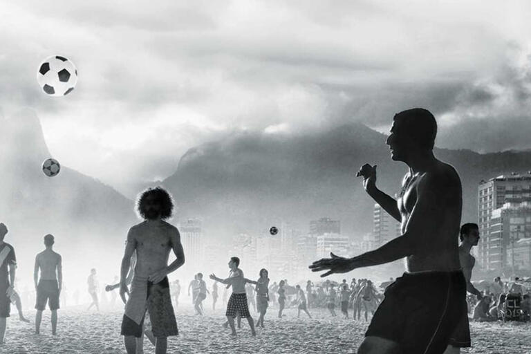 Black and white photo of people playing soccer at the beach in Rio de Janeiro
