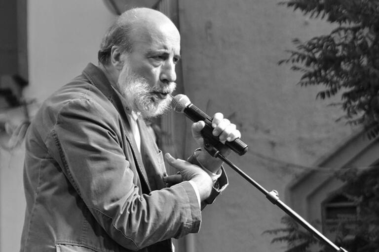 Raúl Zurita holding a microphone with one hand and the other hand over his heart