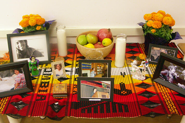 CLAS's altar for the Day of the Dead, colorful table with pictures and flowers