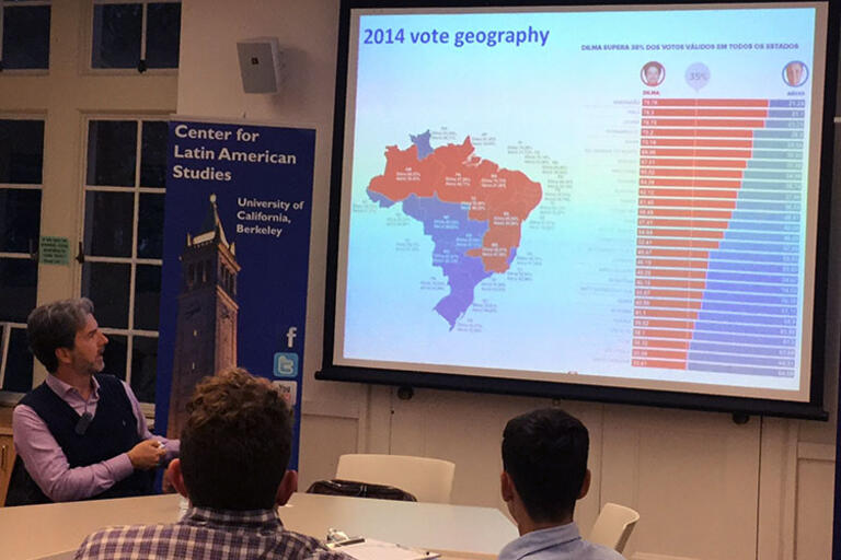 Carlos Milani seating down and showing a map of the regional divide in Brazilian voting