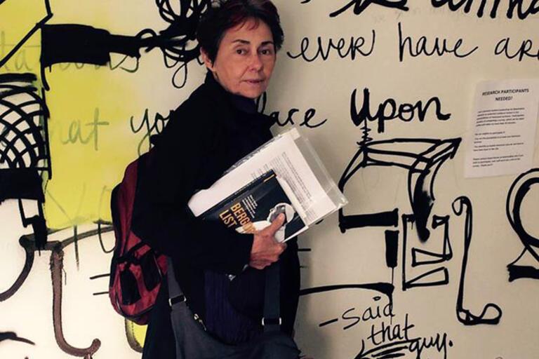 Nancy Scheper-Hughes standing up against a mural in Kroeber Hall