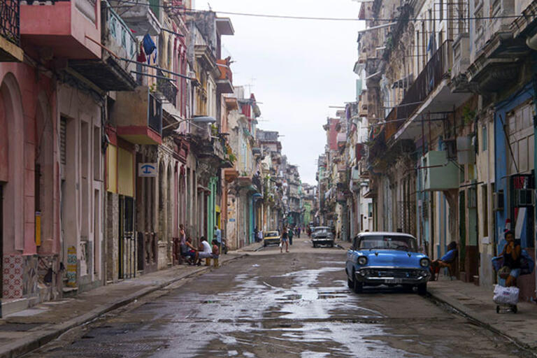 Havana street with old cars and people on the sidewalk