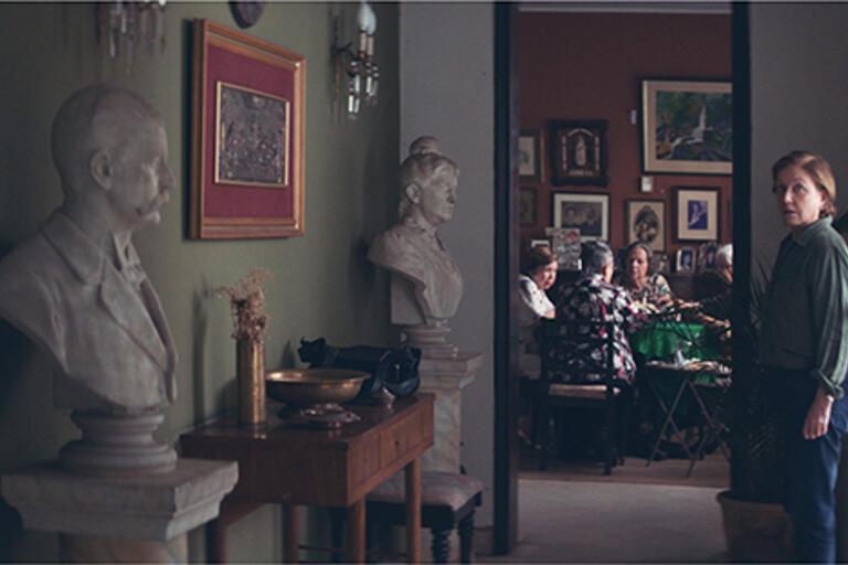 Woman standing at the end of a hallway, behind her there is a round table with four woman playing cards
