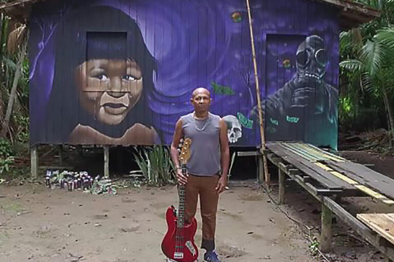 Man standing up with a guitar in front of a purple house