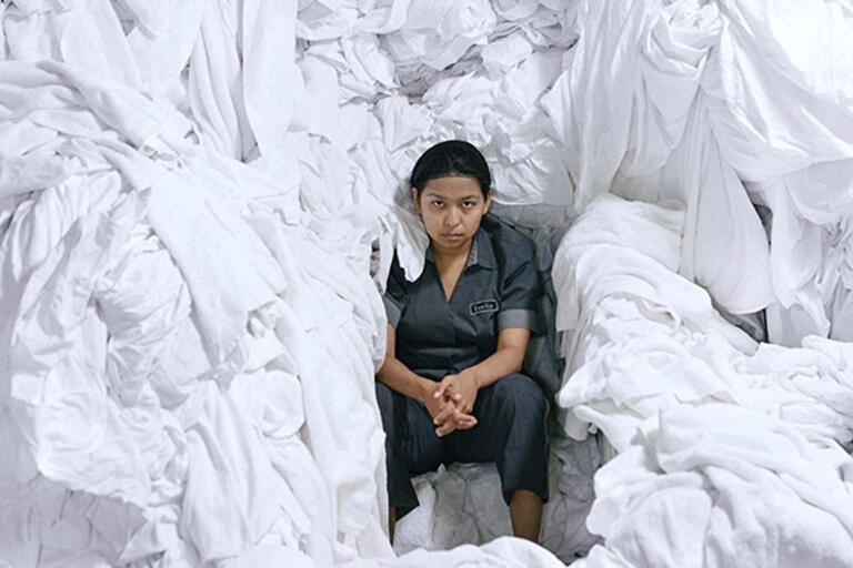 Woman seating surrounded by white bed sheets