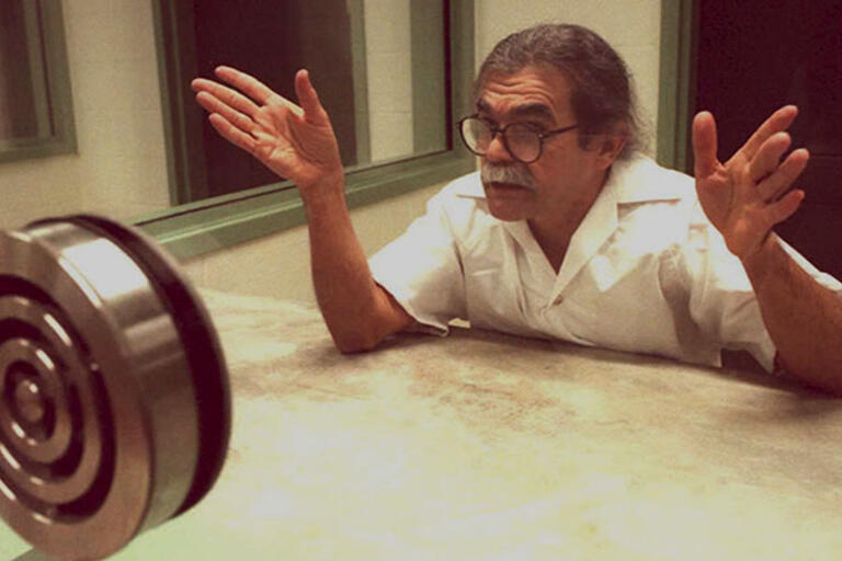 Oscar López Rivera behind a glass being interviewed before his release from prison