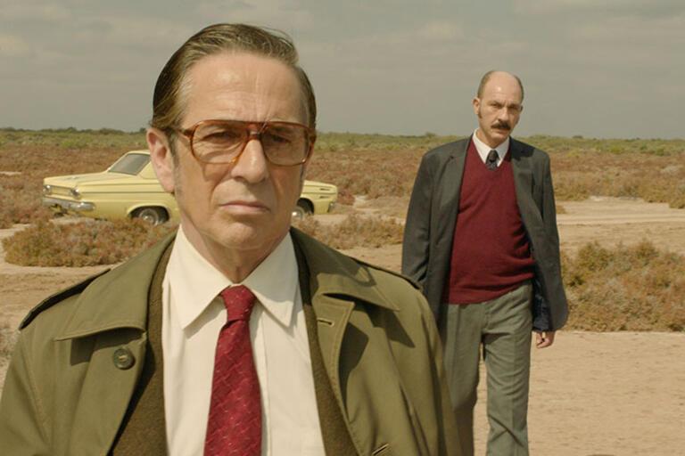 Still from the film Rojo, two men dress as detectives walking in the dessert