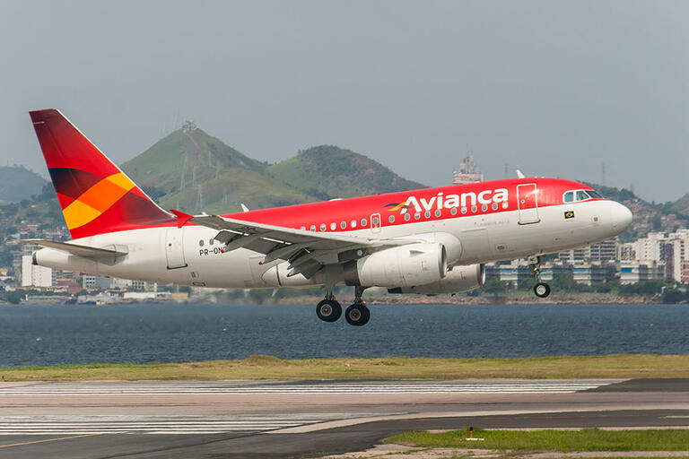 A red airplane with the word Avianca painted in white landing at Rio's Santos Dumont Airport