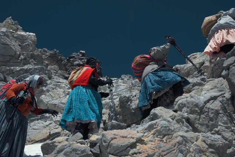 Bolivian Indigenous women climbing the side of a mountain. From Cholitas. (Image courtesy of Arena Comunicación.)