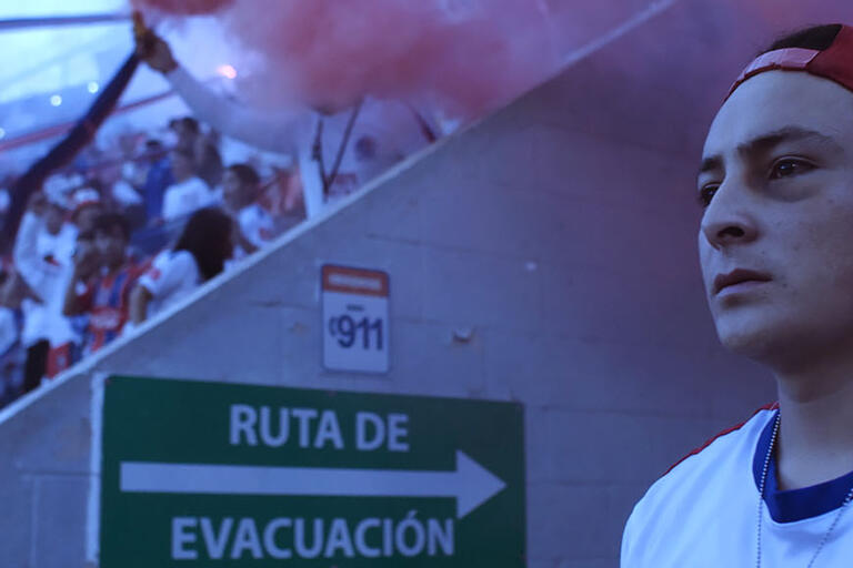 A young man in the entrance to a soccer stadium. Image from 90 Minutos. (Image courtesy of Pulsar.)