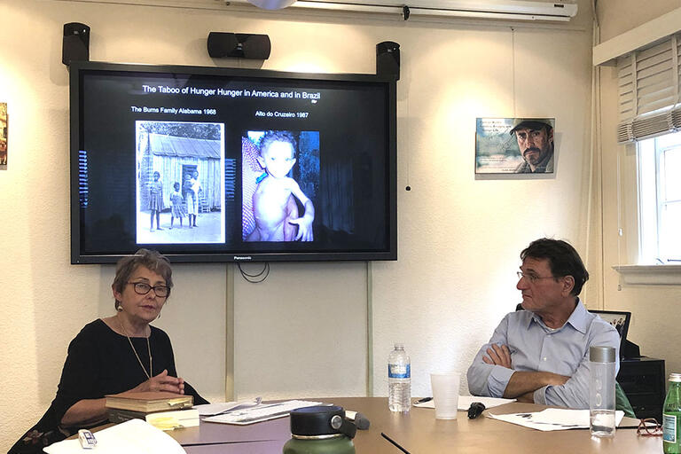 Nancy Scheper-Hughes and Walter Belik seating in a table discussing hunger in Brazil and the U.S.