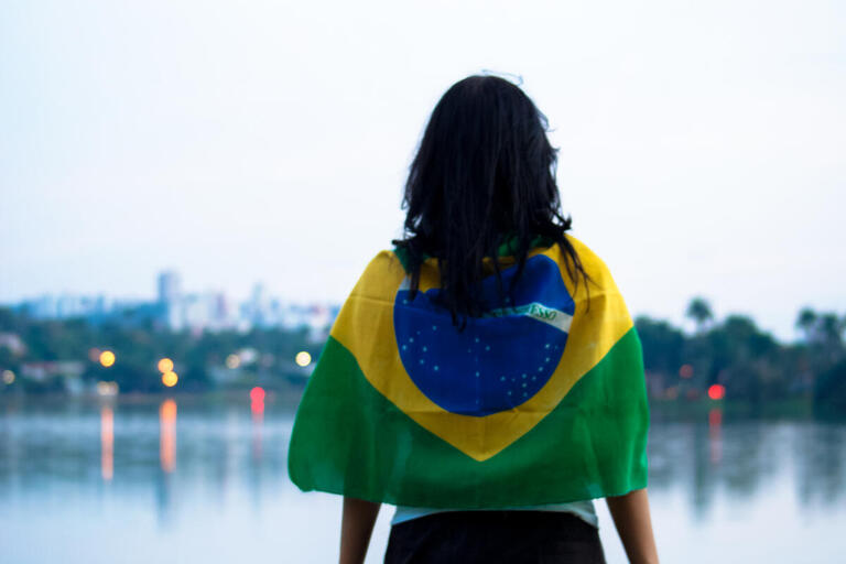 Woman wears a Brazilian flag and looks into the distance.