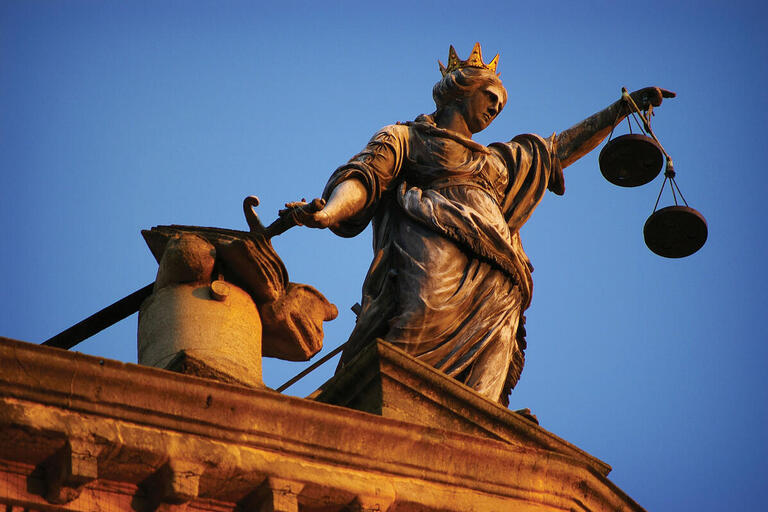 A statue of Justice holding her balanced scales and a sword. (Photo by Jesse Loughborough.)