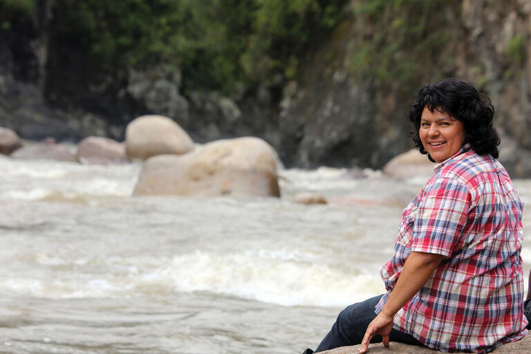 Berta Cáceres sits on a rock in the middle of a river in the Río Blanco region of western Honduras in 2015. (Photo courtesy of the Goldman Environmental Prize.)