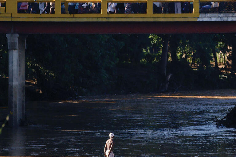 Haitians cross the Massacre River on a bridge into the Dominican Republic near Dajabón. (Photo by and © Herminio Rodríguez.)