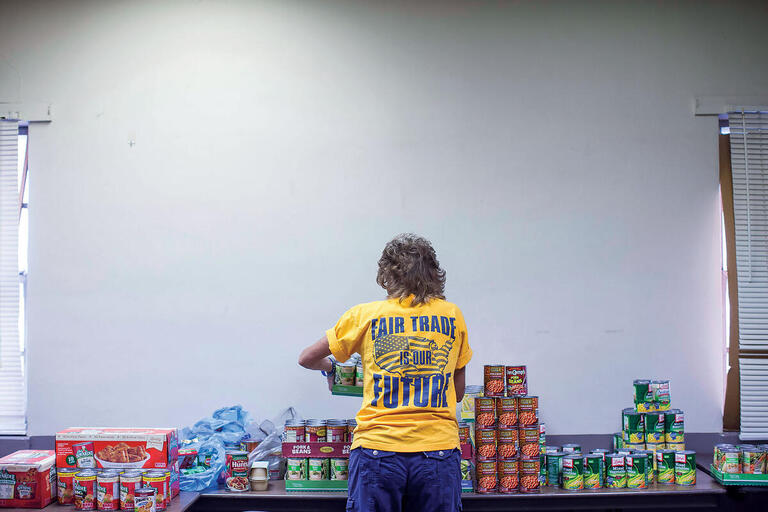 A former steel mill employee in front of a table of canned goods in a union-sponsored food bank in Granite City, Illinois. (Photo by Whitney Curtis for The New York Times.)