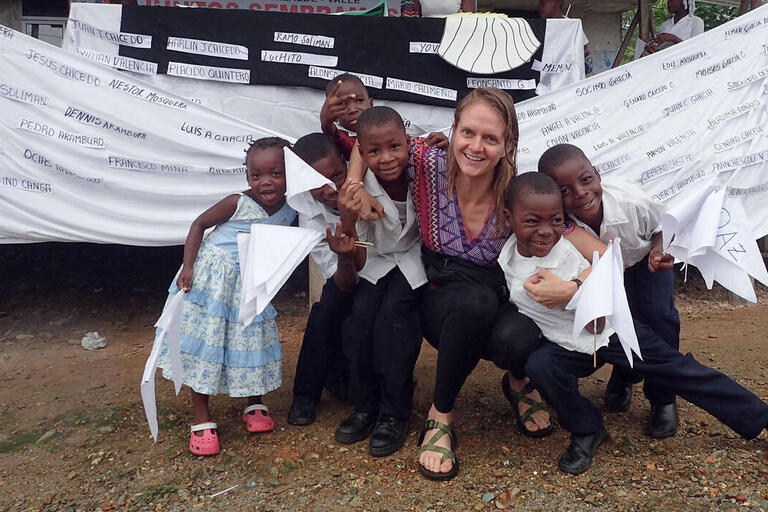 Author Lauren Withey with Colombian children after a peace march with a banner bearing the names of local victims of the conflict. (Photo courtesy of Lauren Withey.)