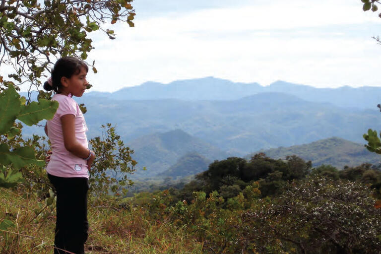 A young girl stands on a hilltop above the site of the El Mozote massacre. (Photo by Allison McKellar.)