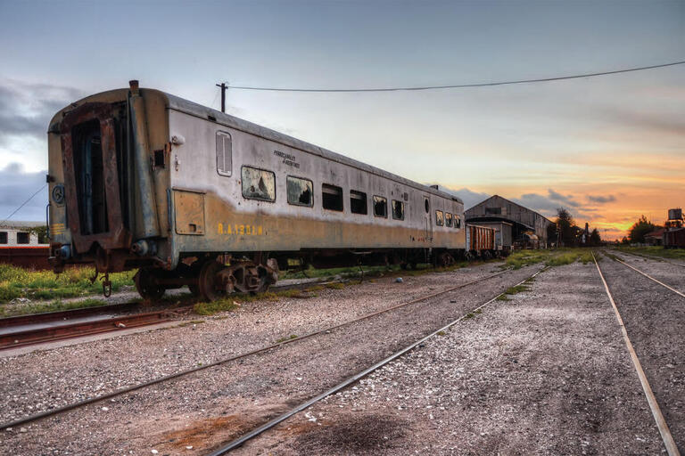 An abandoned railcar sits rusting in a siding and symbolizes the failure of Argentina's rail privatization under neoliberal policies in the 1980s. (Photo by Emilio Küffer.)