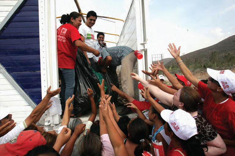 People surround a truck with hands outstretched, waiting for handouts from the Peña Nieto campaign during the 2012 election in San Luis Potosí, Mexico. (Photo by Germán Canseco/Procesofoto.)