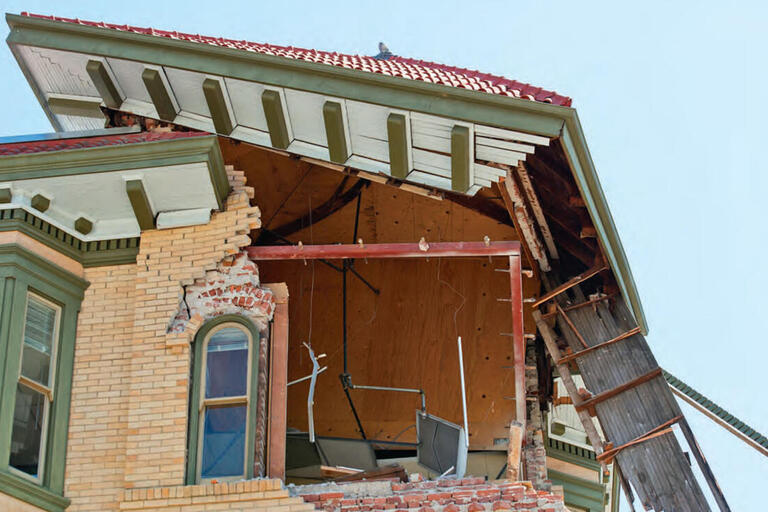 A collapsed brick corner of a building underneath its roof shows damage from the Napa earthquake of August 2014. (Photo by hitchster.)