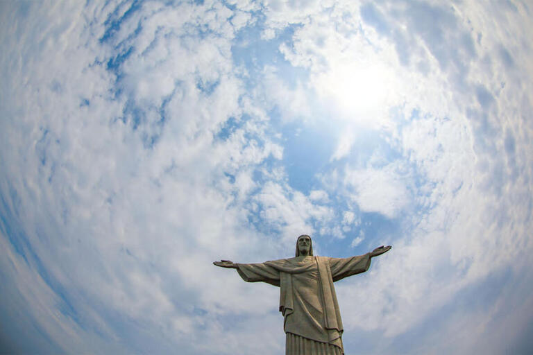 Rio de Janeiro's Cristo Redentor statue outlined against a blue sky and swirling clouds. (Photo by Geraint Rowland.)