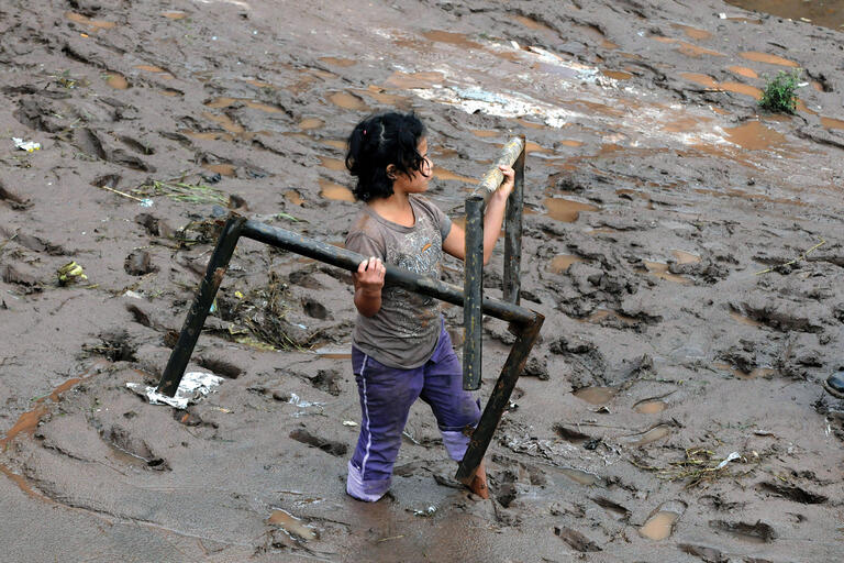A young girl hauls away family possessions though deep mud after a flood in Honduras. (Photo by Globovision.)