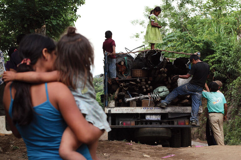 A woman watches neighbors loading possessions on a truck as they flee their homes following gang threats in Tunamiles, El Salvador. (Photo by Salvador Melendez/AP Photo.)