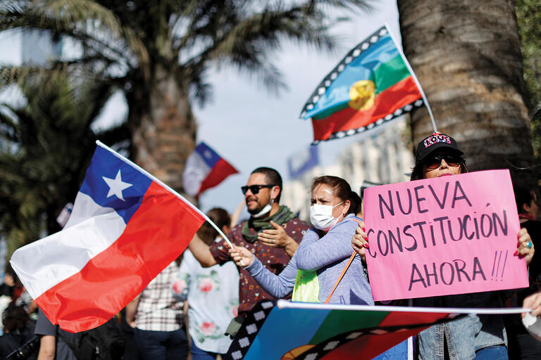 """A woman's sign demands a """"New Constitution Now!!!"""" as Chilean and Mapuche flags fly at a demonstration in Chile, November 2019.  (Photo by Jorge Silva/Reuters.)"""