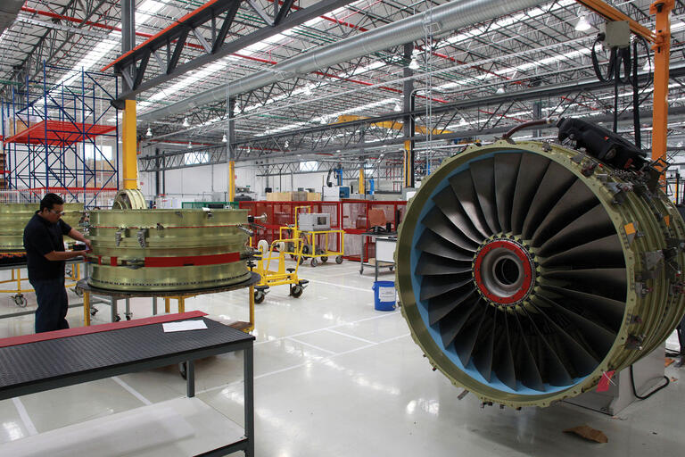 The work floor of an aircraft service center in Querétaro, with a disassembled jet engine. (Photo by francediplomatie.)