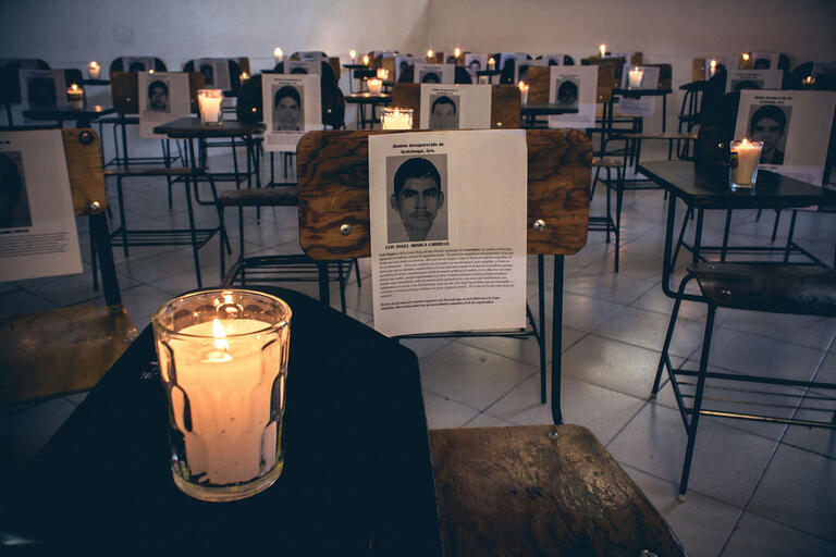 Candles sit on student desks in a memorial to the disappeared students in Ayotzinapa, 2015. (Photo by Uriel López.)