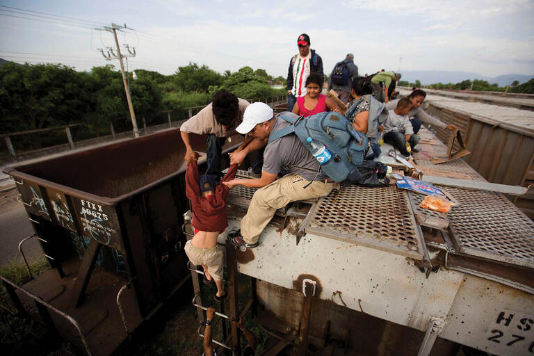 "Migrants in Ixtepec, Mexico, climb on top of the freight train ""La Bestia"" in 2014. (Photo by Eduardo Verdugo/Associated Press.)"