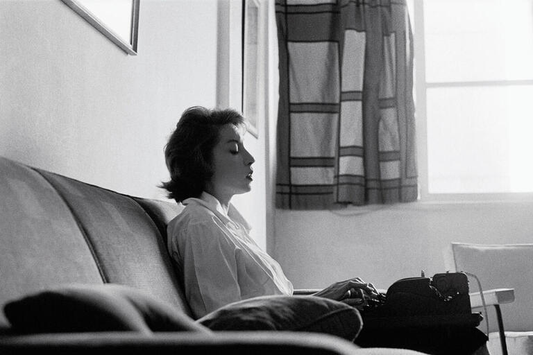Clarice Lispector sits on a couch writing on a typewriter in 1961. (Photo by Claudia Andujar.)