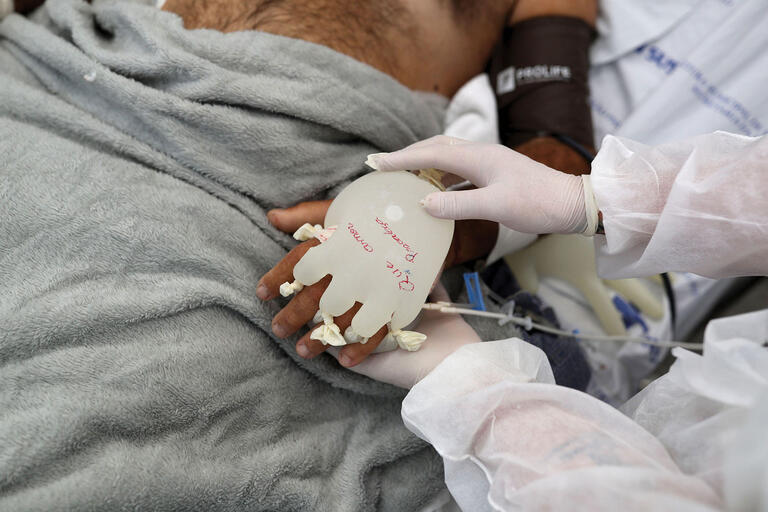 """A nurse puts a warm water-filled glove on a Covid-19 patient in Brazil, April 2021. The phrase on the glove reads """"May love prevail."""" (Photo by Amanda Perobelli/REUTERS.)"""
