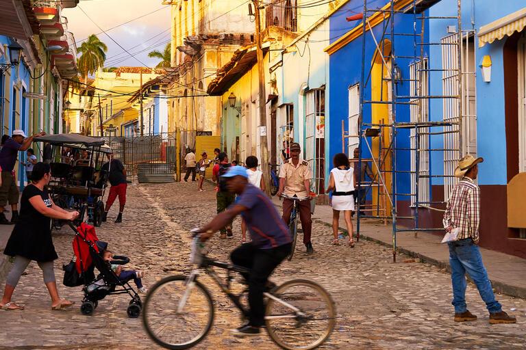 Street scene, people walking and biking in front of colorful buildings