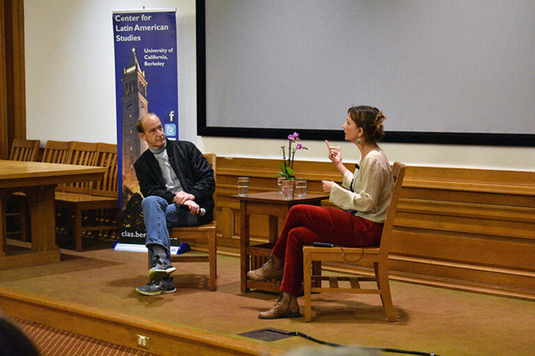 Petra Costa and Charles Ferguson seating in conversation with each other