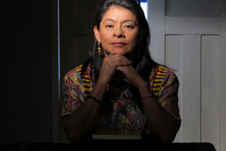A woman stares intently at the camera with hands folded.
