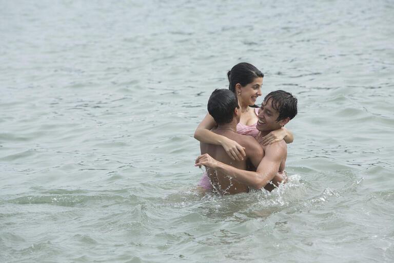 Three people hug in the ocean.