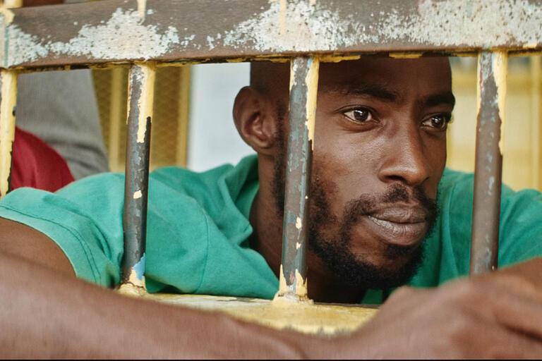 A man looks through bars.