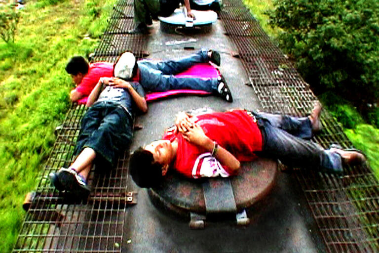 Children lie on top of a train as it moves through the countryside