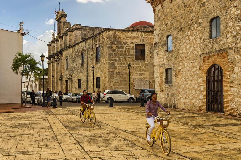 Two people ride bikes through Santo Domingo