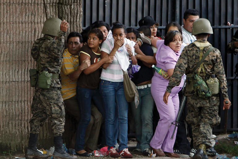 Honduran army soldiers surround supporters of ousted President Manuel Zelaya during the coup in Tegucigalpa, June 2009. (Photo by Eduardo Verdugo/AP Photo.)
